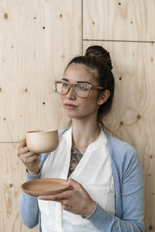 Young woman working in creative office, taking a break, drinking coffee from wooden cup - RIBF00797