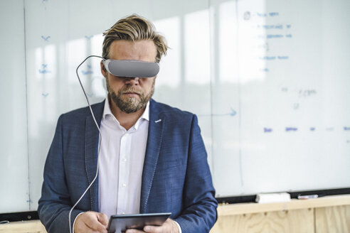 Businessman standing in office, using VR glasses and digital tablet - RIBF00809
