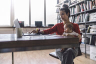 Working mother with baby on her lap, sitting in office, using laptop - RIBF00824