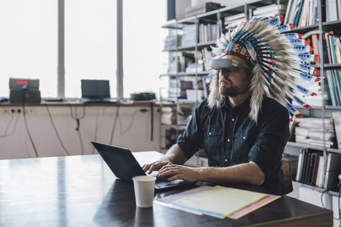 Man wearing Indian headdress and VR glasses in office, using laptop - RIBF00827