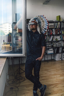 Man wearing Indian headdress and VR glasses in office, looking out of window - RIBF00830