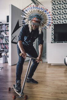 Man wearing Indian headdress and VR glasses in office, using kick scooter - RIBF00833