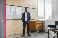 Businessman standing in his office in front of whiteboard, with hands in pockets - RIBF00848