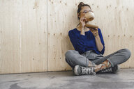 Young woman taking a break in office, drinking coffee from a wooden cup - RIBF00851
