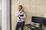 Working father standing in office, holding his son - RIBF00854