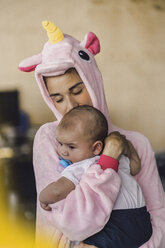 Young mother wearing unicorn onesie, standing in office, holding her son in her arms - RIBF00863