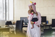 Young mother wearing unicorn onesie, standing in office, holding her son in her arms - RIBF00866
