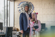 Man and woman, dressed as Indian and unicorn, standing in office, woman holding baby in her arms - RIBF00869