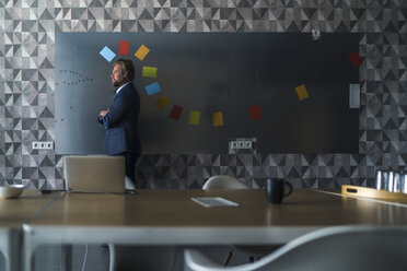 Businessman standing in front of magnet wall with a colorful headdress, made from sticky notes - RIBF00875