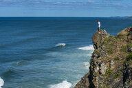 Australia, Queensland, Byron Bay, man standing on a rock, cliff at Cape Byron - RUNF00421