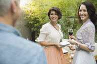 Women standing by dining table outdoors - HEROF00101