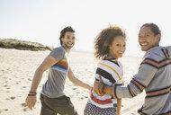 Portrait of cheerful friends running on beach - HEROF00152