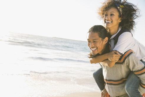 Man piggybacking woman on beach - HEROF00179