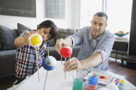 Father and son preparing solar system model at home - HEROF00302