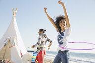 Couple hula hooping on beach - HEROF00332
