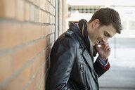 Smiling man answering smart phone outdoors - HEROF00539