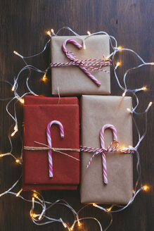 Wrapped Christmas presents with decorations and lights on wooden background - FSIF03406