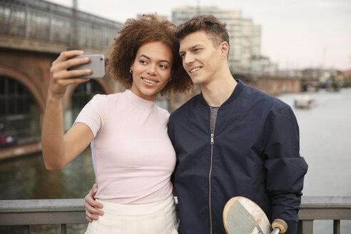 Young couple with smart phone taking selfie on bridge - FSIF03454