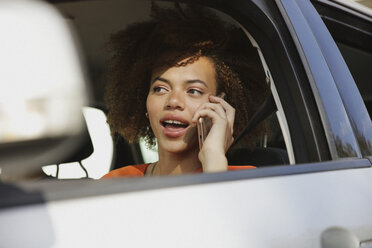 Young woman talking on smart phone and driving car - FSIF03460