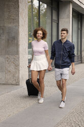 Young couple with suitcase walking on urban sidewalk - FSIF03466