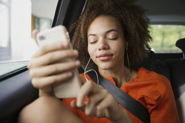 Serene young woman listening to music with headphones and mp3 player in back seat of car - FSIF03472