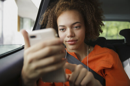 Young woman listening to music with headphones and mp3 player in car - FSIF03484