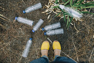 Personal perspective woman standing at littered plastic water bottles - FSIF03496