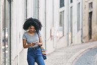 Young woman using smart phone on urban street - FSIF03508