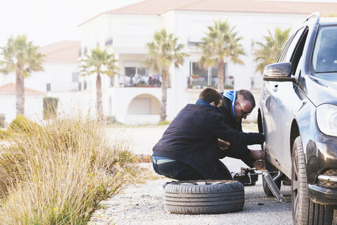 Father and son changing car tire at roadside - FSIF03520