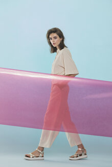 Portrait of a female fashion model posing with pink plastic sheet against blue background - FSIF03529