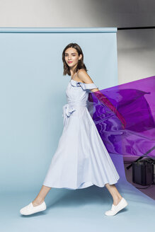 Portrait of a female fashion model posing with purple plastic sheet against blue background - FSIF03535