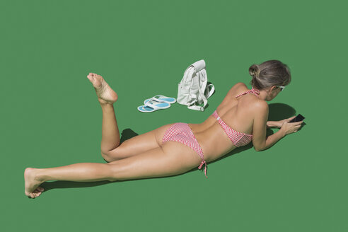 Woman in bikini sunbathing on green background - FSIF03538