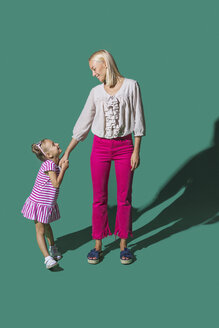 Mother and daughter holding hands on green background - FSIF03544