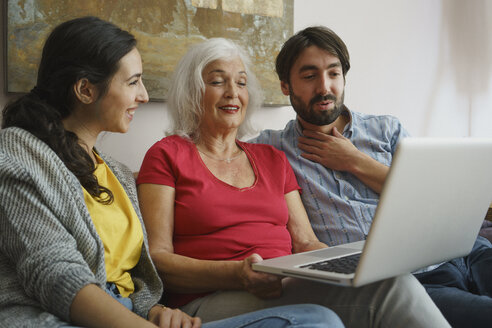 Senior mother using laptop with daughter and son on living room sofa - FSIF03586