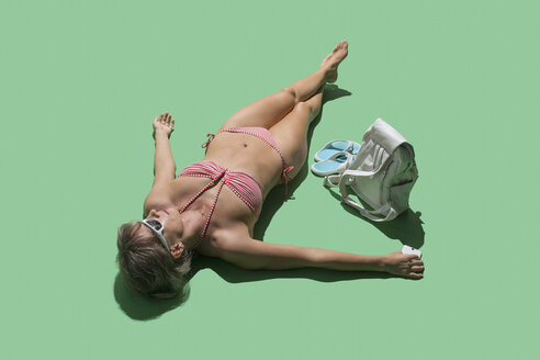 Woman in bikini sunbathing on green background - FSIF03631
