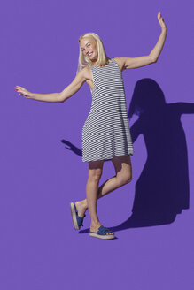 Portrait carefree woman in striped dress against purple background - FSIF03643