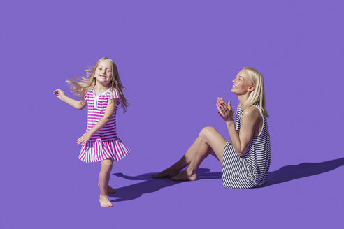 Mother watching daughter dancing on purple background - FSIF03649