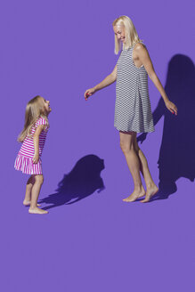 Carefree mother and daughter in striped dresses dancing against purple background - FSIF03652