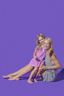 Portrait smiling mother and daughter hugging in striped dresses against purple background - FSIF03655