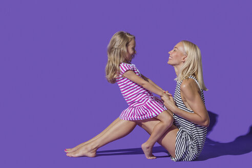 Mother and daughter in striped dresses on purple background - FSIF03658