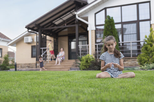 Girl sitting in grass in backyard - FSIF03670