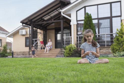 Girl sitting in grass in backyard - FSIF03670