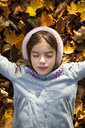 Portrait of little girl lying on autumn leaves - LVF07604