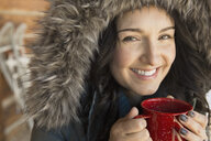 Portrait of woman in fur hood drinking coffee outdoors - HEROF00587