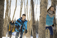Siblings running through winter forest - HEROF00611