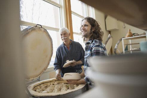 Pottery technicians standing by kiln - HEROF00704