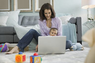 Mother with baby using laptop in living room - HEROF00803