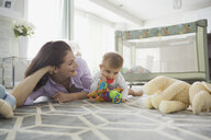 Mother and baby girl playing with toys on floor - HEROF00812