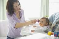 Mother feeding baby girl in high chair at home - HEROF00815