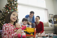 Girl holding doll with family at Christmas - HEROF00824
